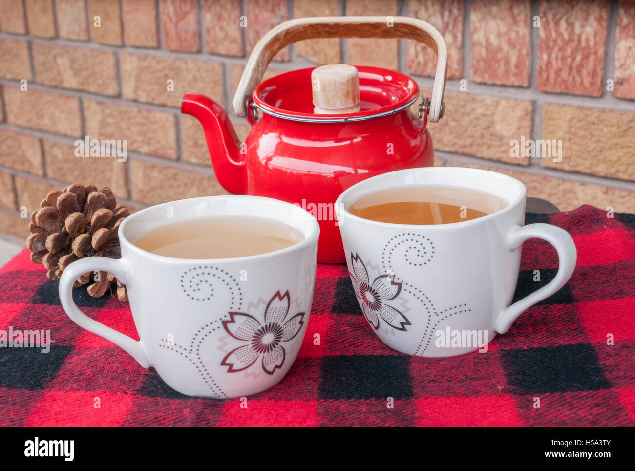Two teacups on a cozy winter throw with red teapot and pinecone. - Stock Image