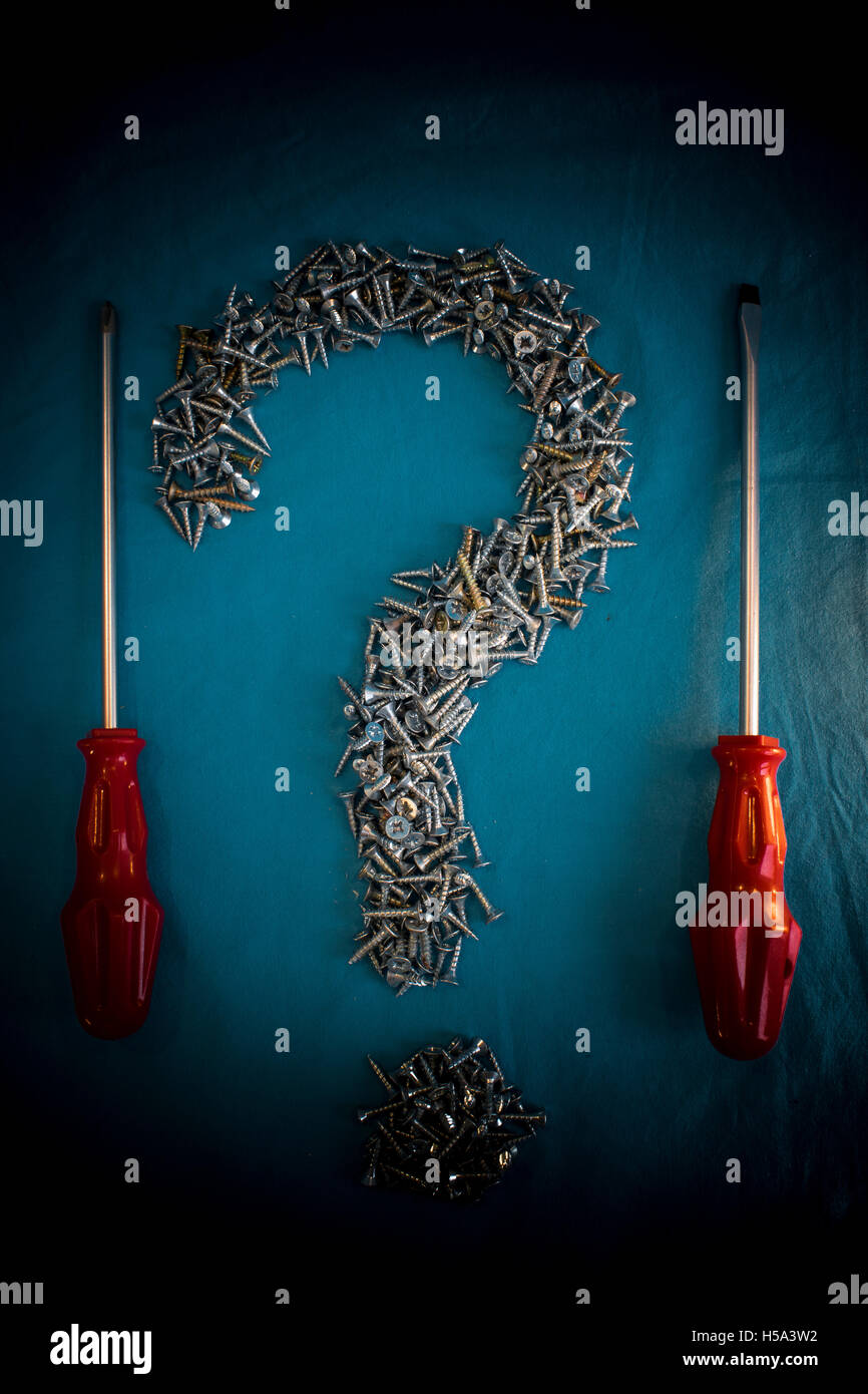 Pile of Screws in the form of Question Mark and diferent Screwdrivers - Stock Image