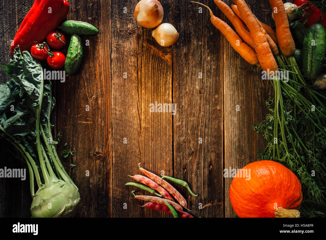 Frame of vegetables over wooden table with copy space - Stock Image
