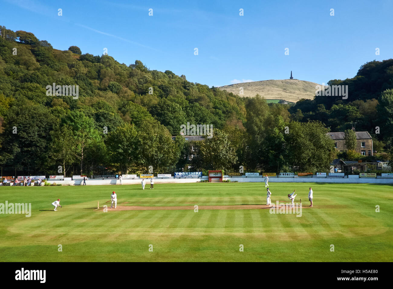 Cricket match taking place on a clear, sunny day in Yorkshire with a monument on the hillside behind. - Stock Image