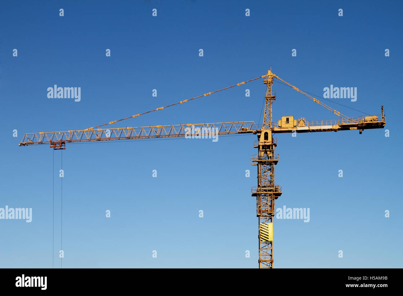 The building tower crane against the blue sky - Stock Image