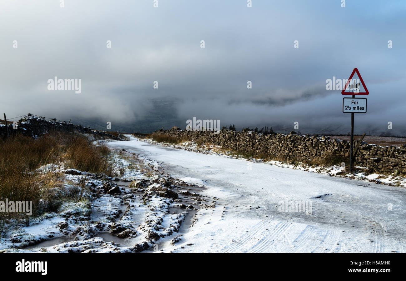Slippery going for all users on the snow covered Coal Road above Dentdale, Cumbria, Yorkshire Dales, National Park, - Stock Image
