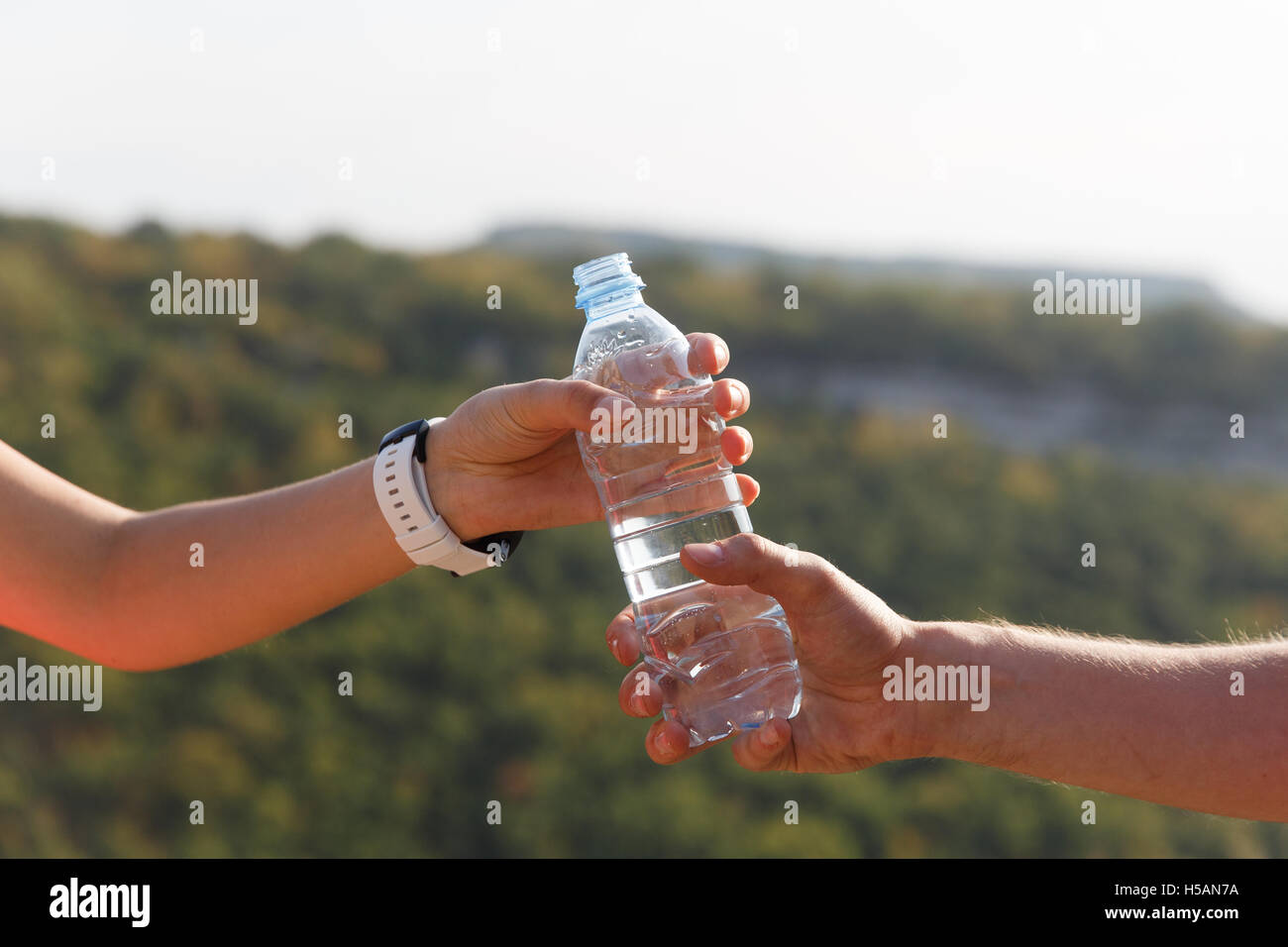 Male and female hand holding water bottle on nature background - Stock Image