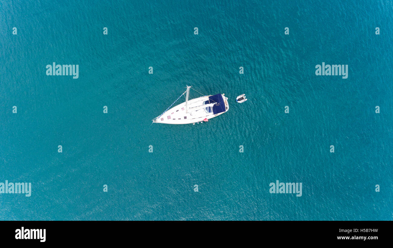 Top view of sailing yacht with a small pontoon floating in the middle of calm sea turquoise, green waters - Stock Image