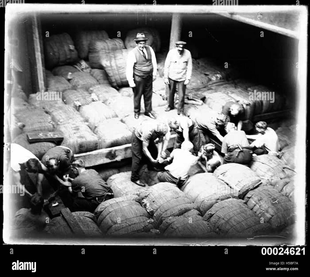 Men packing and securing bales of wool for transport in the hold of the MAGDELENE VINNEN, March 1933 - Stock Image