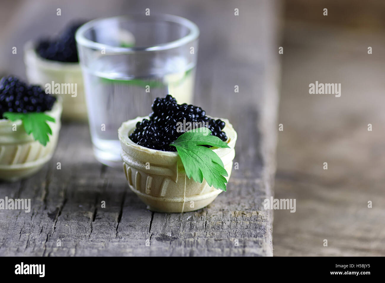 black caviar on a wooden background - Stock Image
