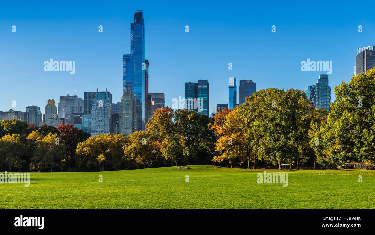 Central Park Sheep Meadow with full autumn colors. Midtown Manhattan skyscrapers in early morning light. New York - Stock Image
