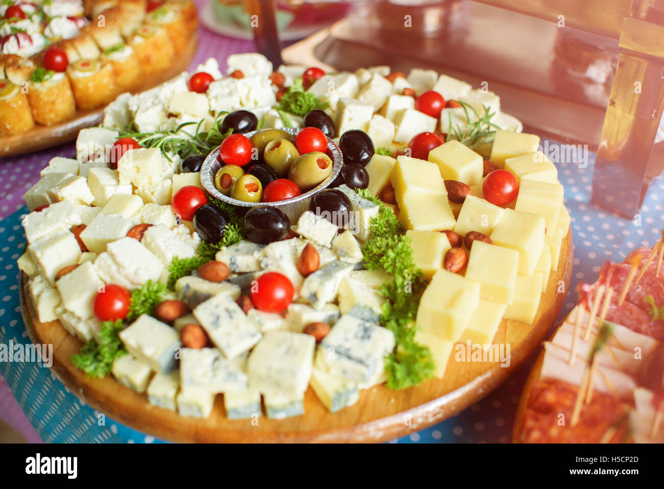 White and yellow cheese, tomato and olives on wooden plate Stock Photo