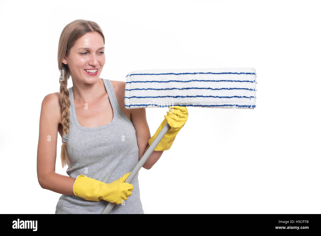 Cleaning concept. Smiling, happy woman with floor mop and yellow rubber gloves - Stock Image