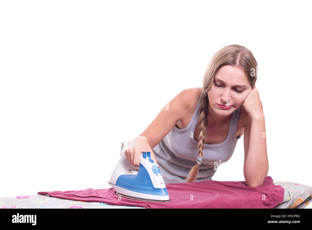 Bored sad young woman ironing clothes Stock Photo
