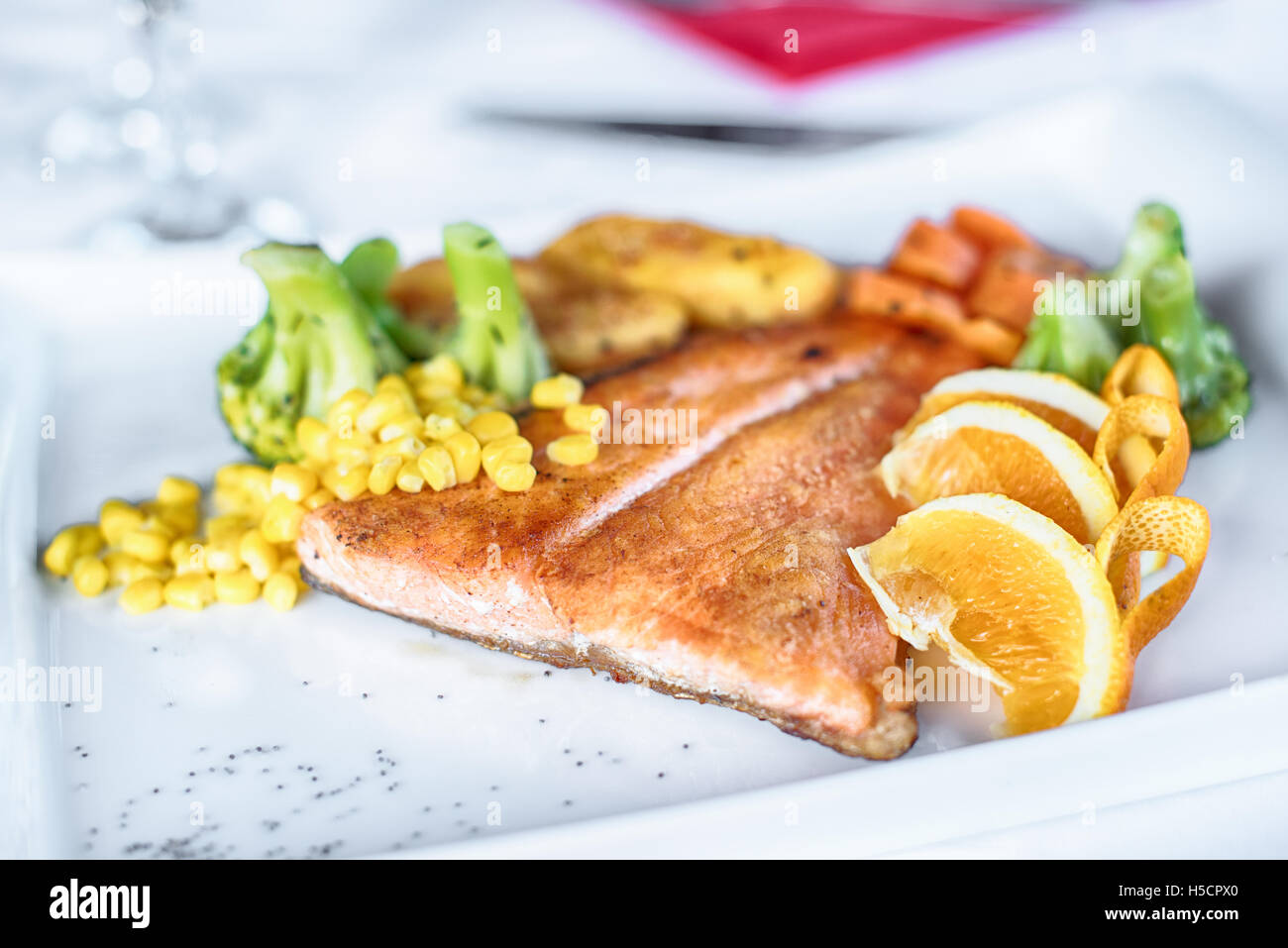 Grilled salmon with spring vegetables on white plate Stock Photo