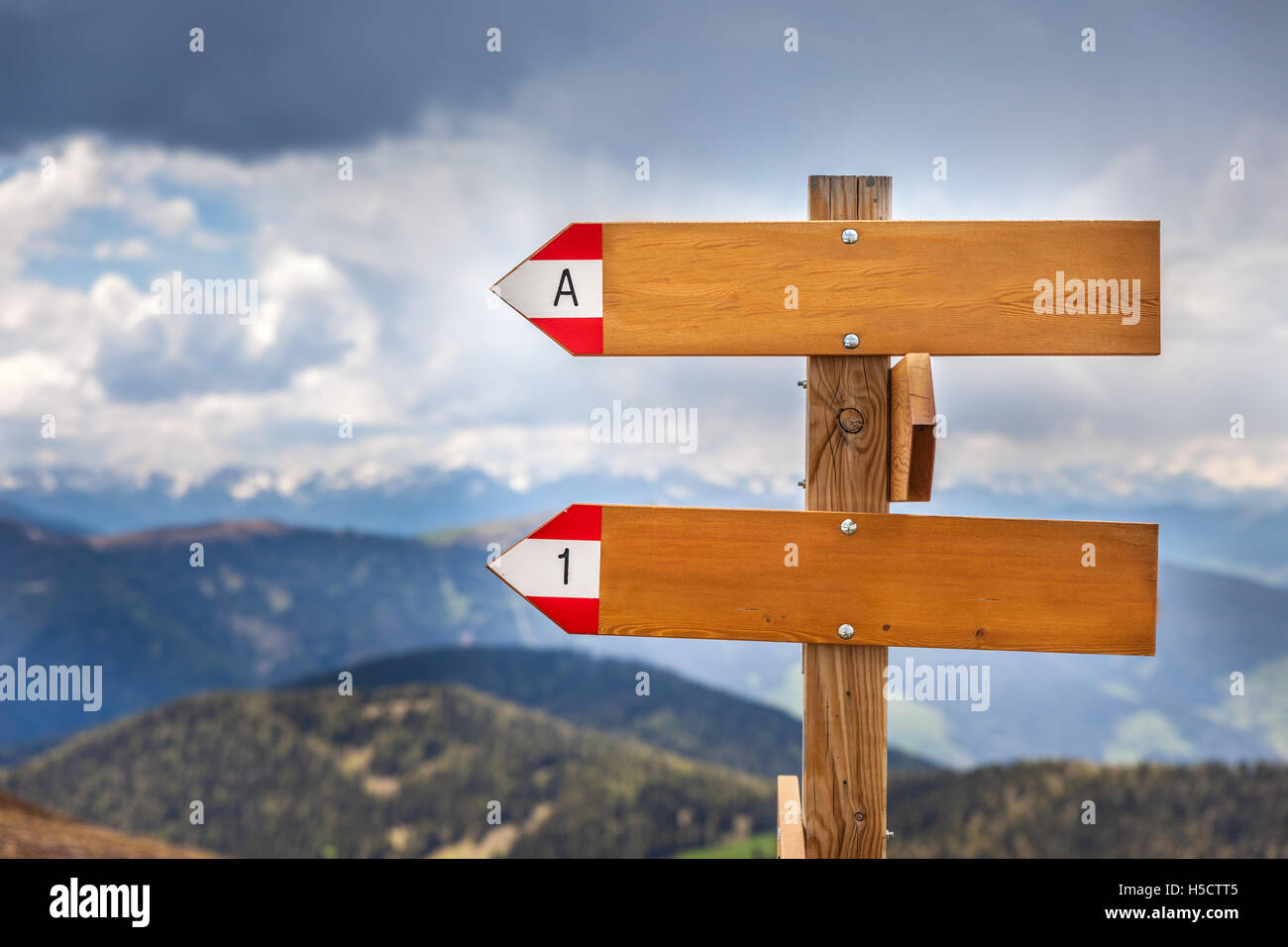Empty wooden signpost in the mountains with bad weather - Stock Image