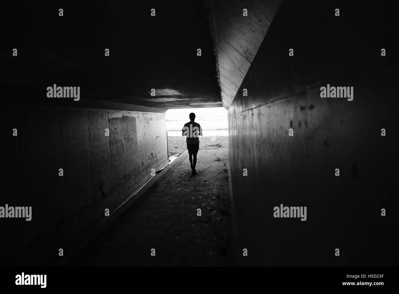 Edgy black and white photograph of a man walking through a tunnel