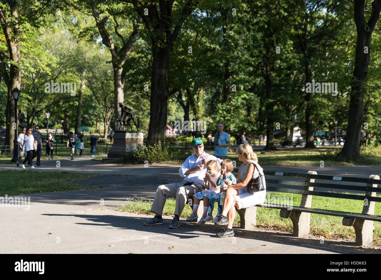 Family, parents and two children, sitting on a bench and eating ice creams - enjoying time together on a sunny day - Stock Image
