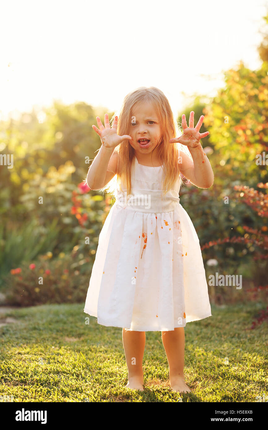 25c4e047f69 Nice little girl in a white dress dirty scares. Dress in tomato juice. A girl  stands barefoot on the lawn.