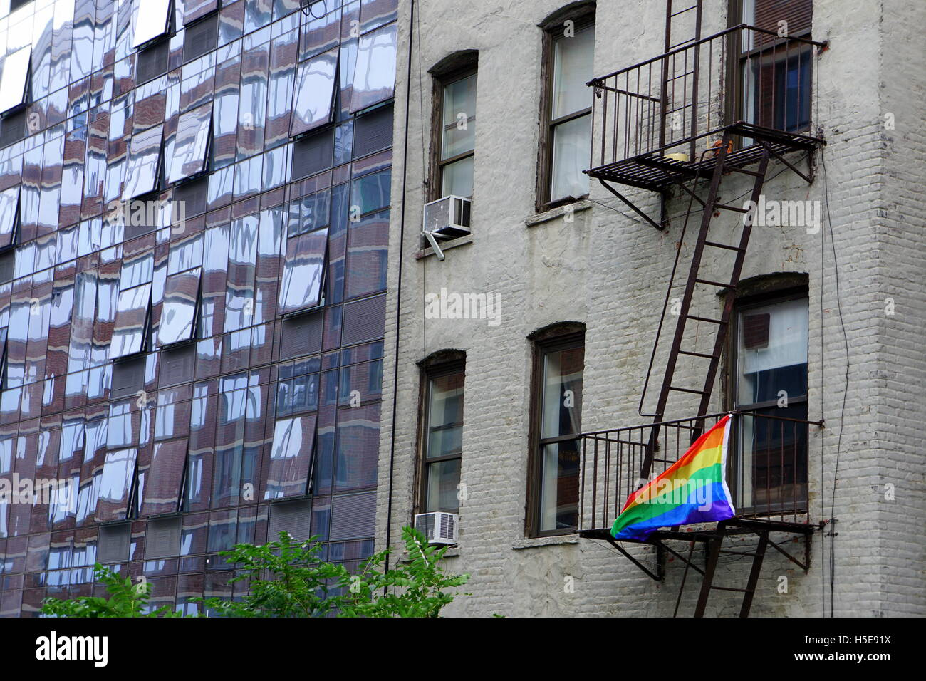 Gay pride flag (rainbow flag) hanging on the fire escape of an old apartment building, Chelsea, New York City, NY, Stock Photo