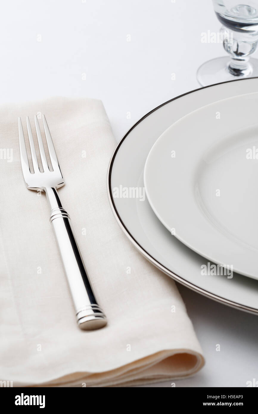 Fine dining table setting place setting with high quality classic style white china dishes, linen napkin and silverware - Stock Image