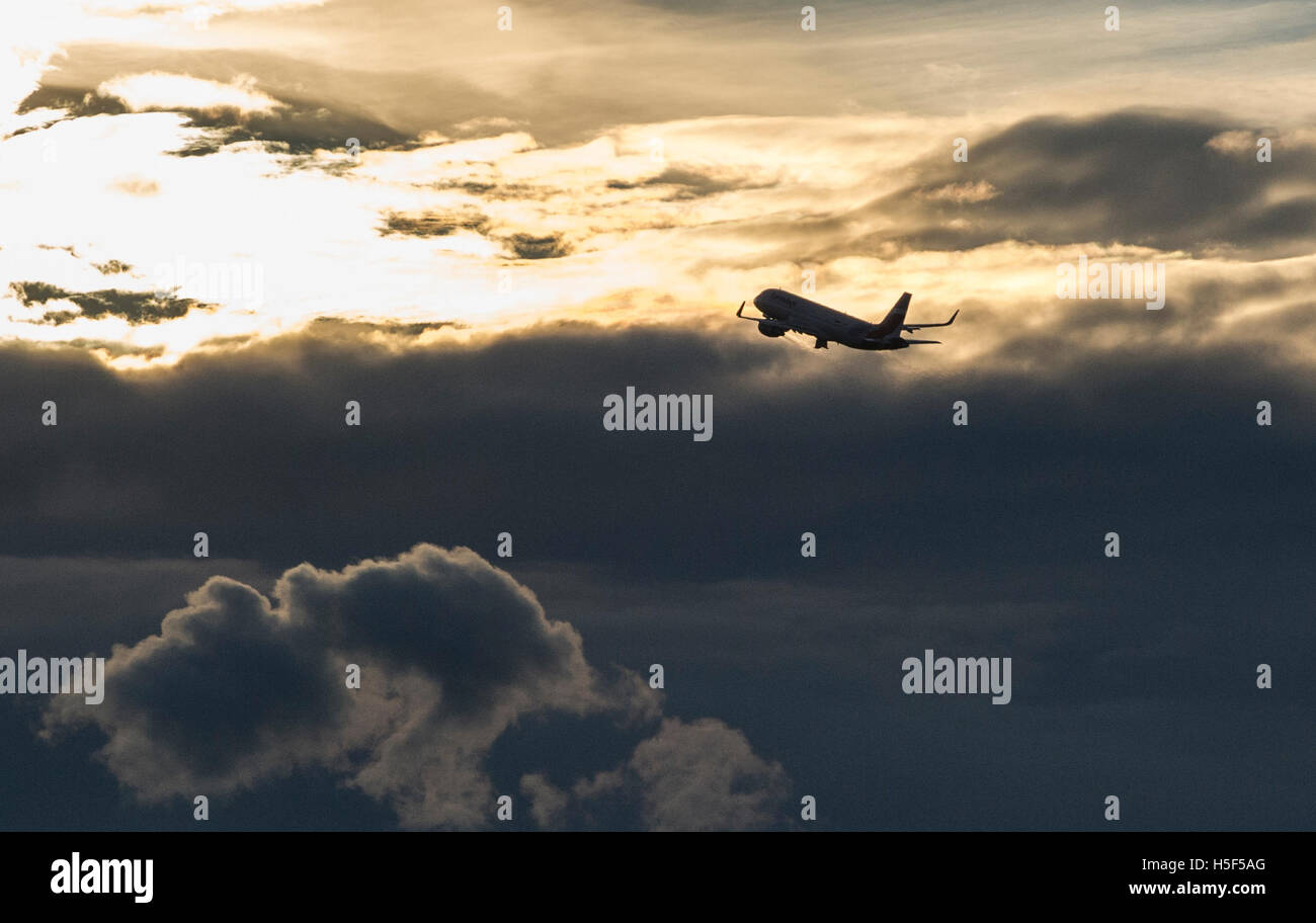 Berlin, Germany. 20th Oct, 2016. A plane flying past dark clouds towards the sun at Tegel airport in Berlin, Germany, Stock Photo