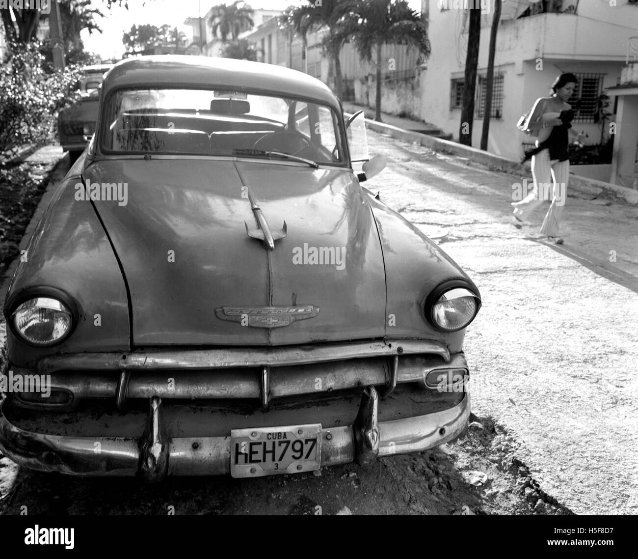 Havana, CUBA. 15th Feb, 2006. Young Cuban girl walks past one of many Cuban Maquinas, aka Yank tanks or pre 1960 Stock Photo