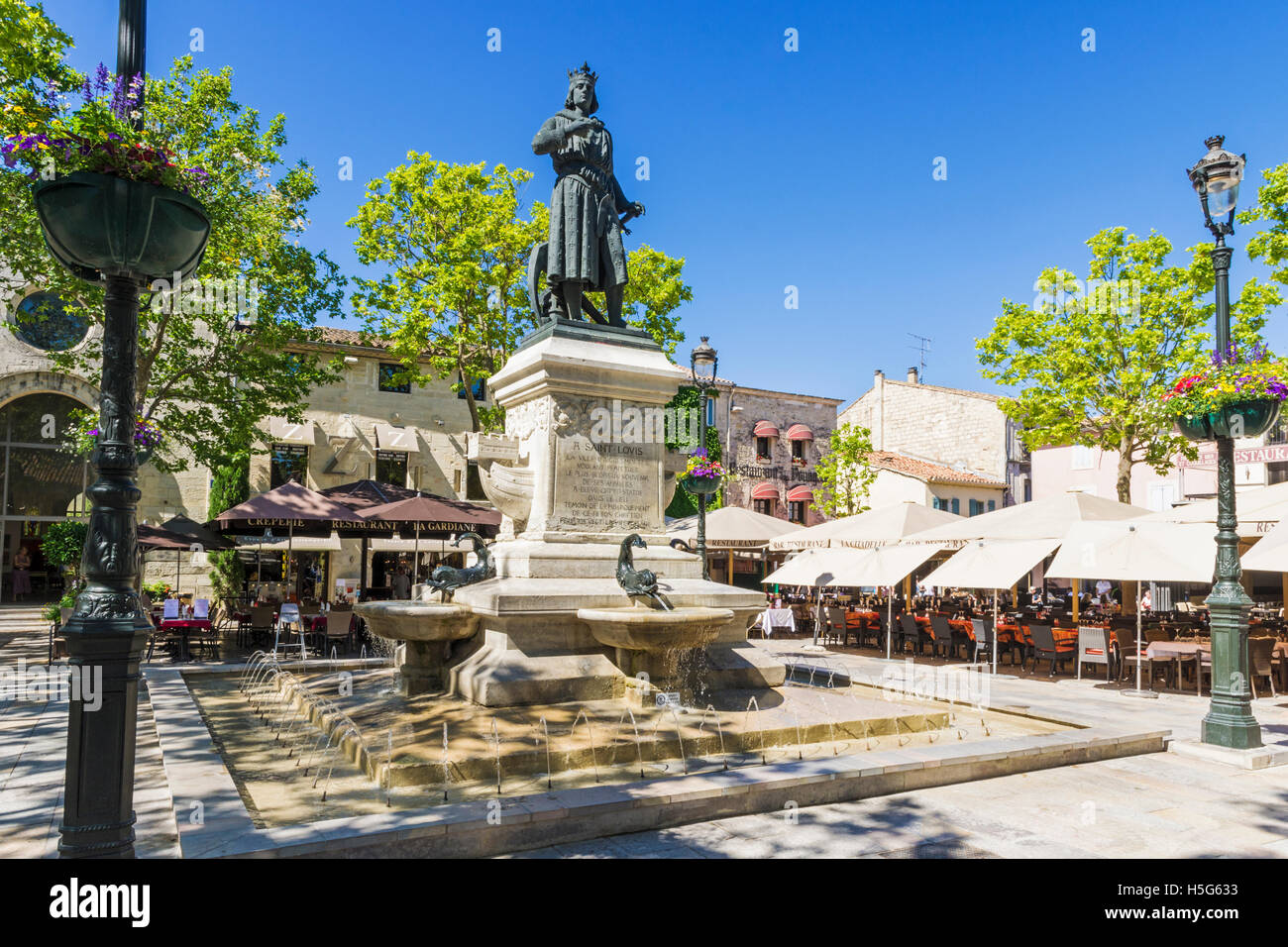 Statue of Saint Louis on a fountain plinth in the cafe lined Place Saint-Louis, Aigues Mortes, Nimes, Gard, France - Stock Image