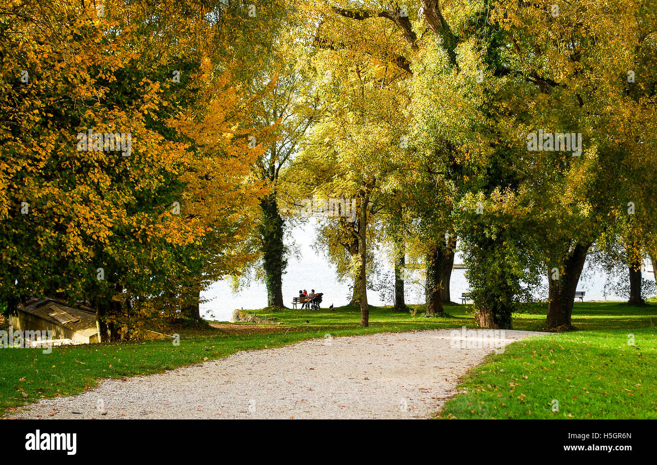 People enjoying a warm autumn afternoon at Lake Chiemsee in Germany Stock Photo