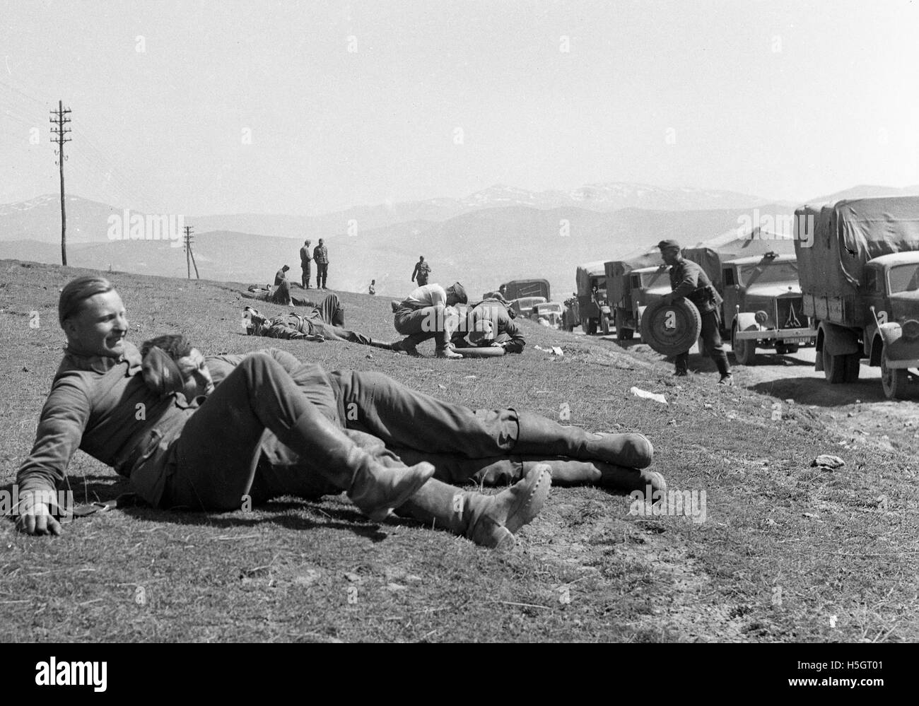 German soldiers relaxing and repairing tyre puncture in the Ardennes region France during World War Two - Stock Image