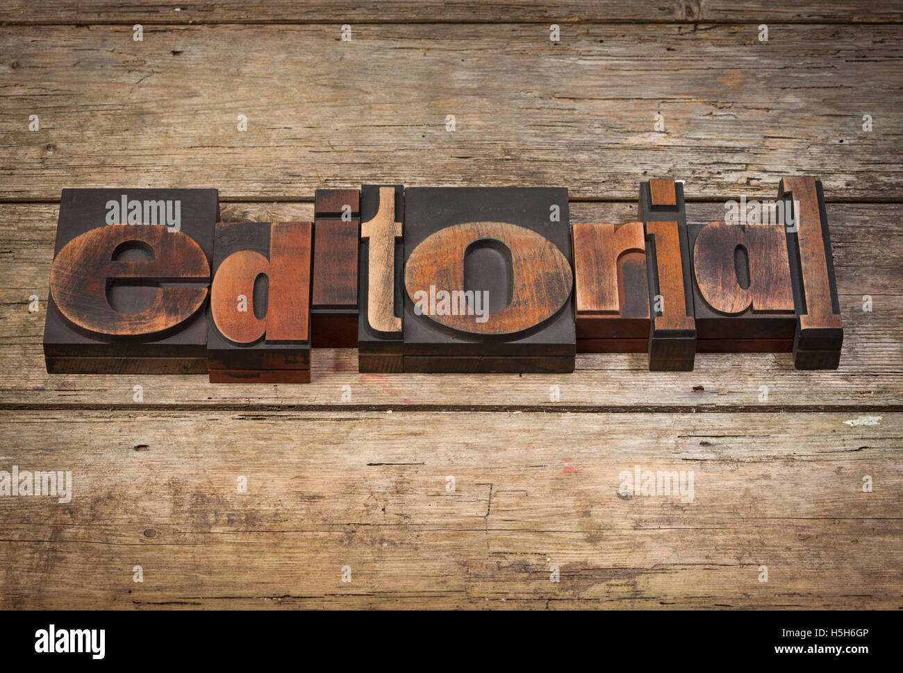 editorial, word written with vintage letterpress printing blocks on rustic wooden background - Stock Image