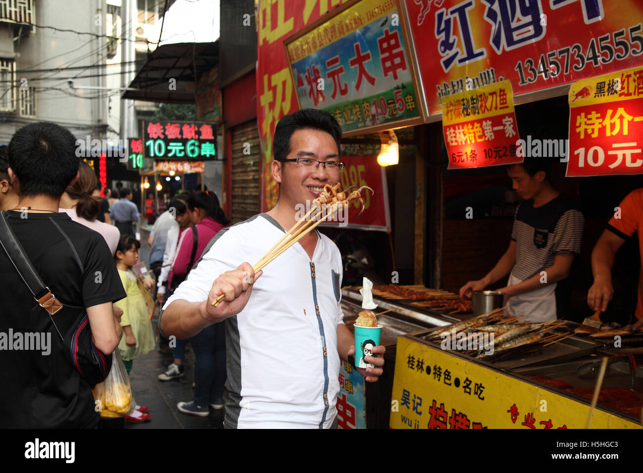A young Chinese man smiles while eating squids on skewers in front of a fast food stand. The market in Guilin, China. - Stock Image