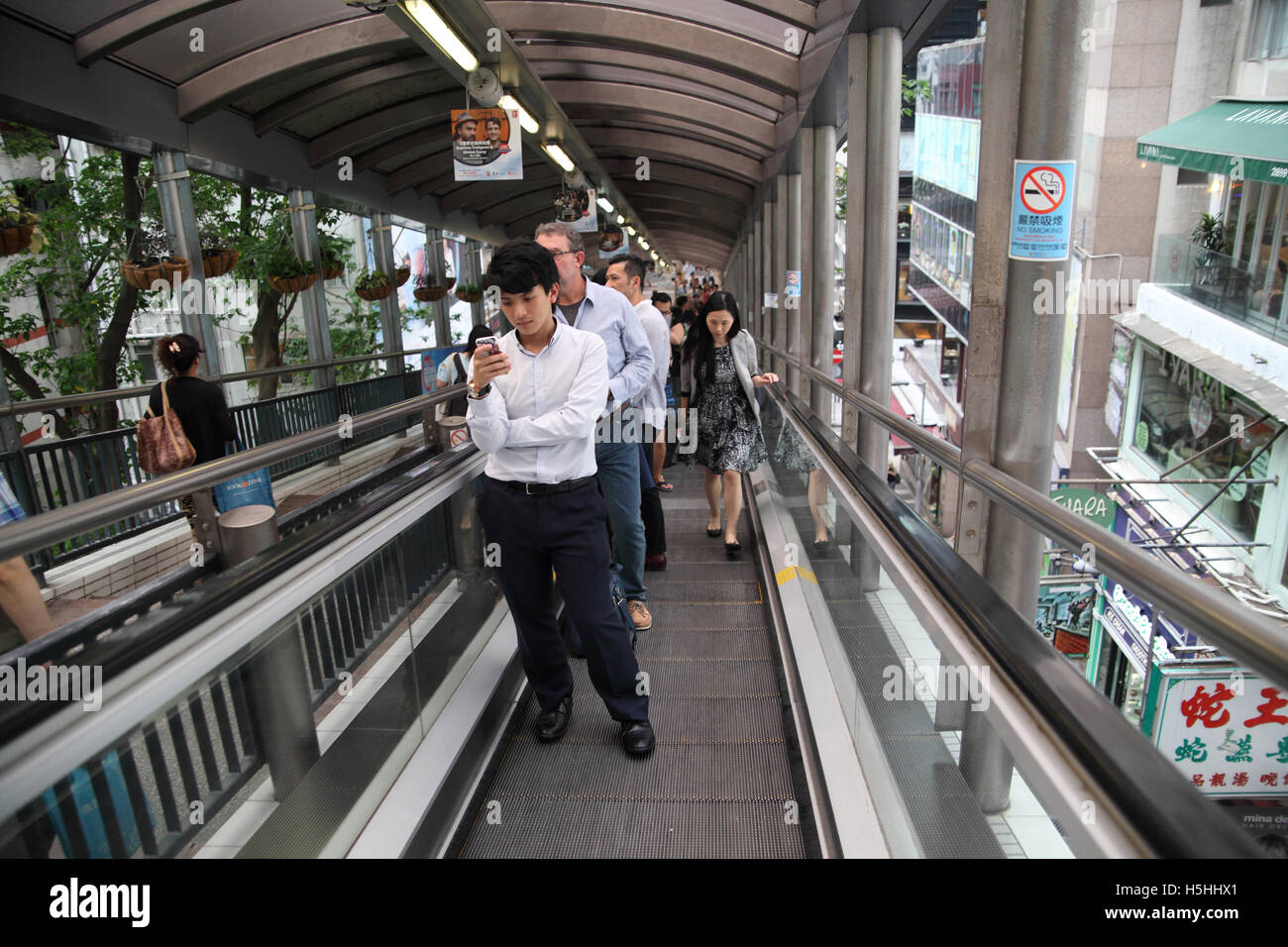 People on an escalator, some stand and use the smartphones others rush by and take over. Central to Mid-Levels escalator - Stock Image