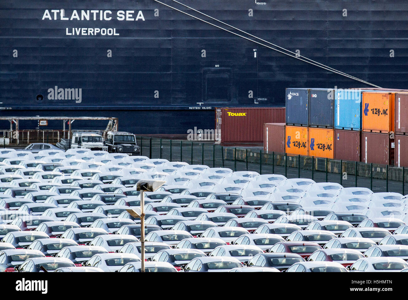 Luxury cars under wraps, wrapped for protection for export from the UK at Seaforth Docks.   White wrapped covered - Stock Image