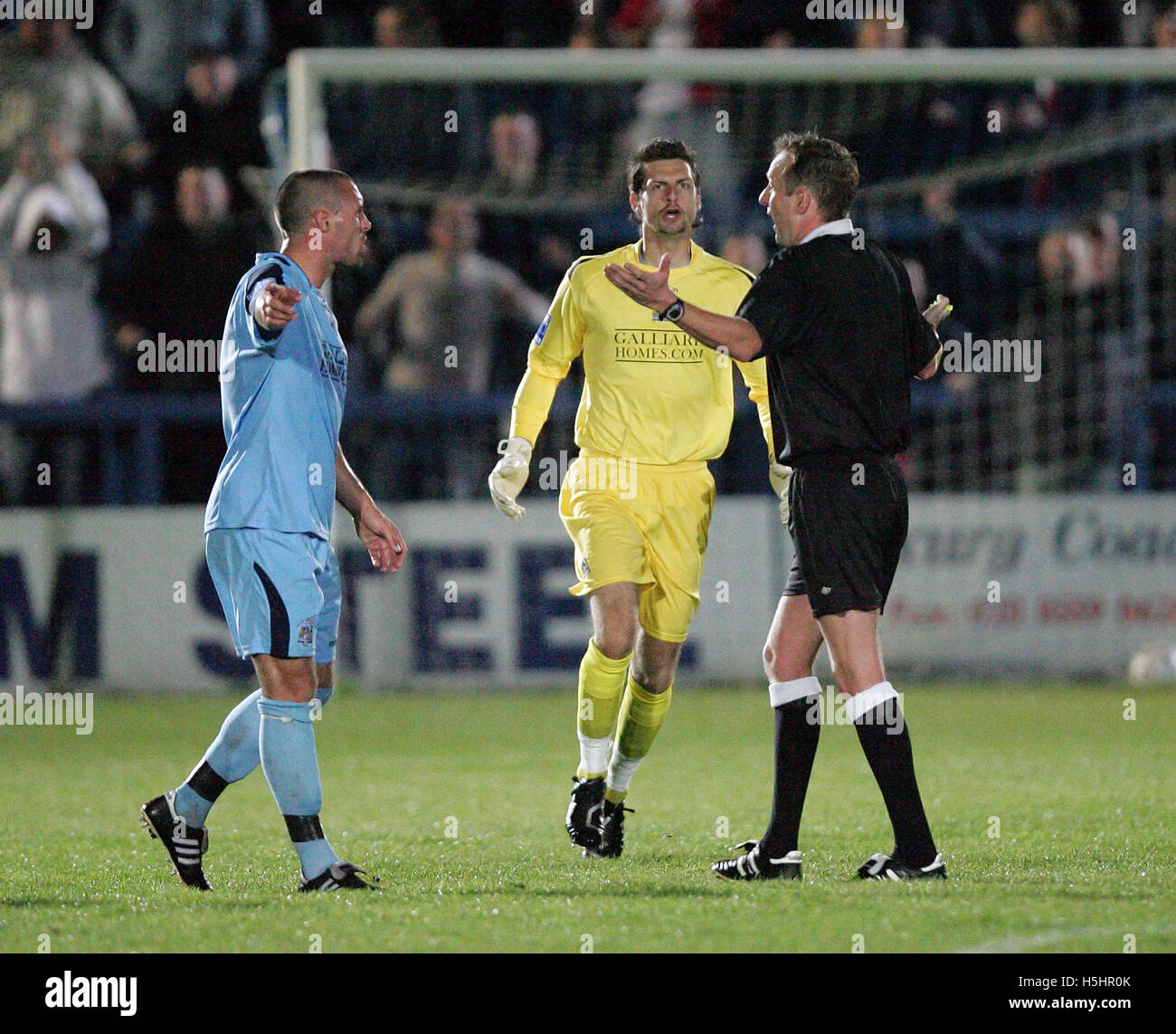 Jamie Stuart and Ross Flitney of Grays protest to Referee Ian Cooper after Matt Pattison of Woking had netted a Stock Photo