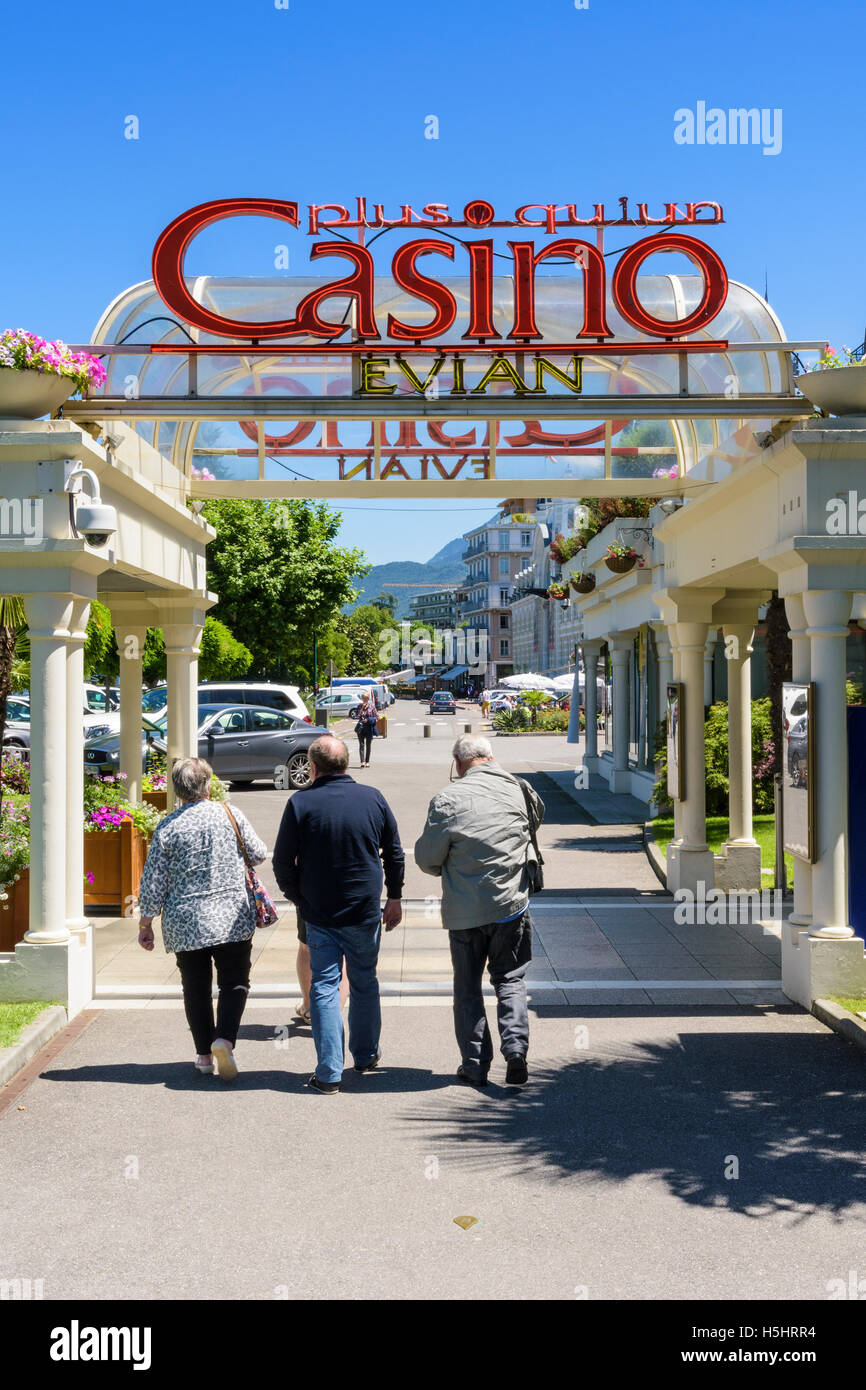 People walking under the sign of the historic Casino d'Evian, Évian-les-Bains, France - Stock Image