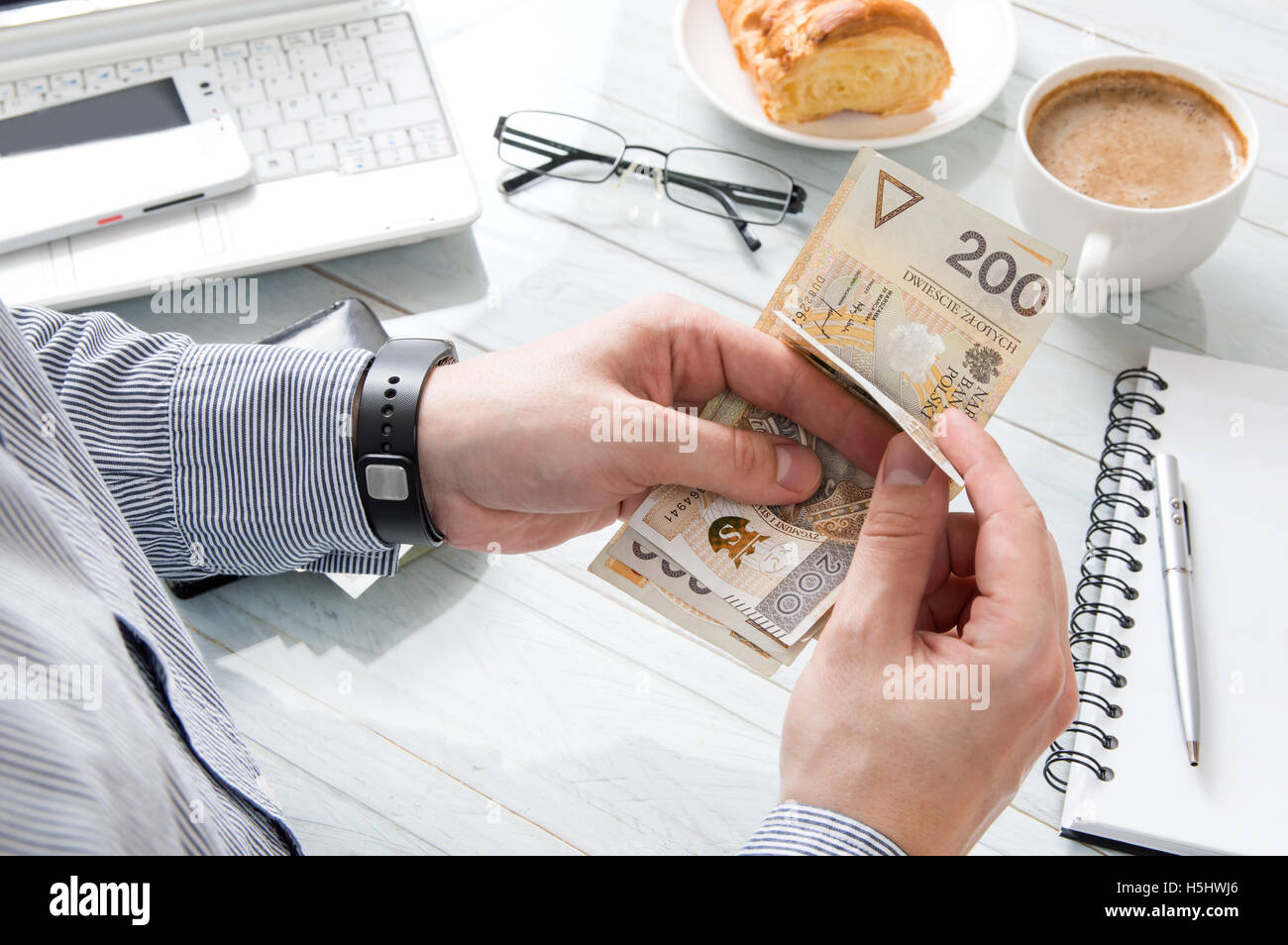 Businessman is counting money at breakfast in the work - Stock Image