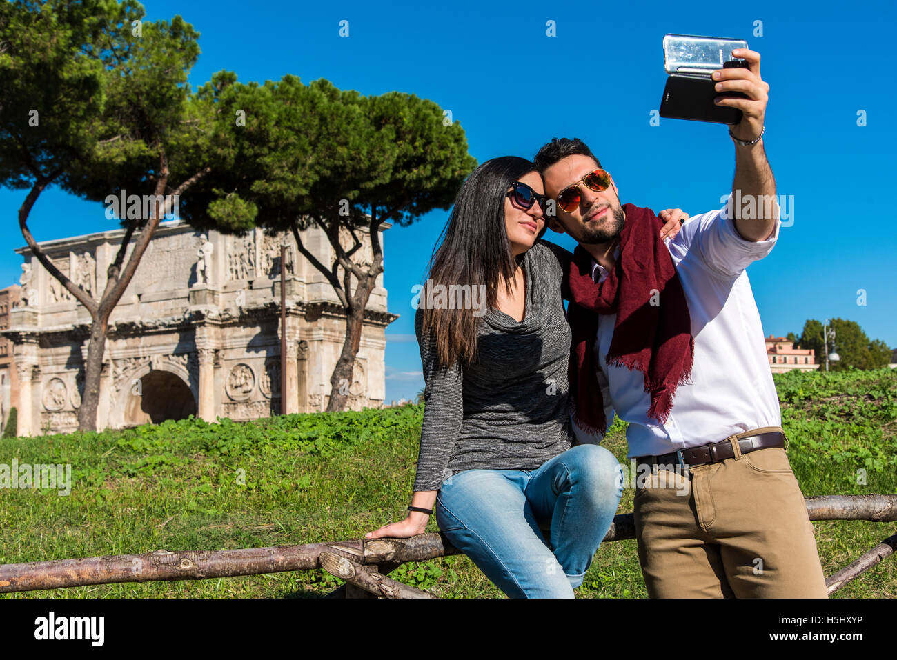 Young caucasian couple taking a selfie with a smartphone in front of the Arch of Constantine, Rome, Lazio, Italy - Stock Image
