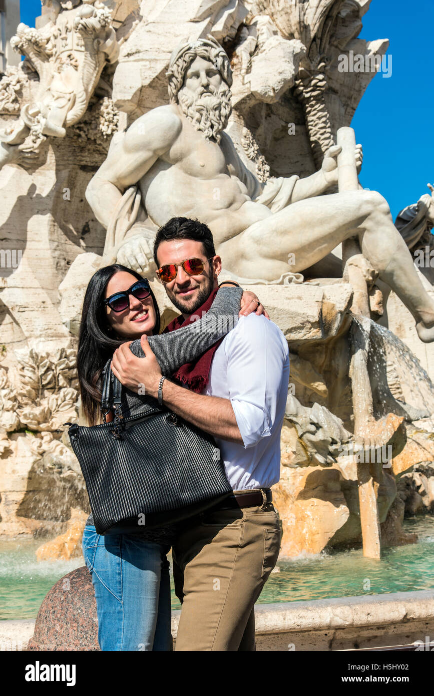 Tourist couple embrace in front of Fountain of the four Rivers in Piazza Navona, Rome, Lazio, Italy - Stock Image