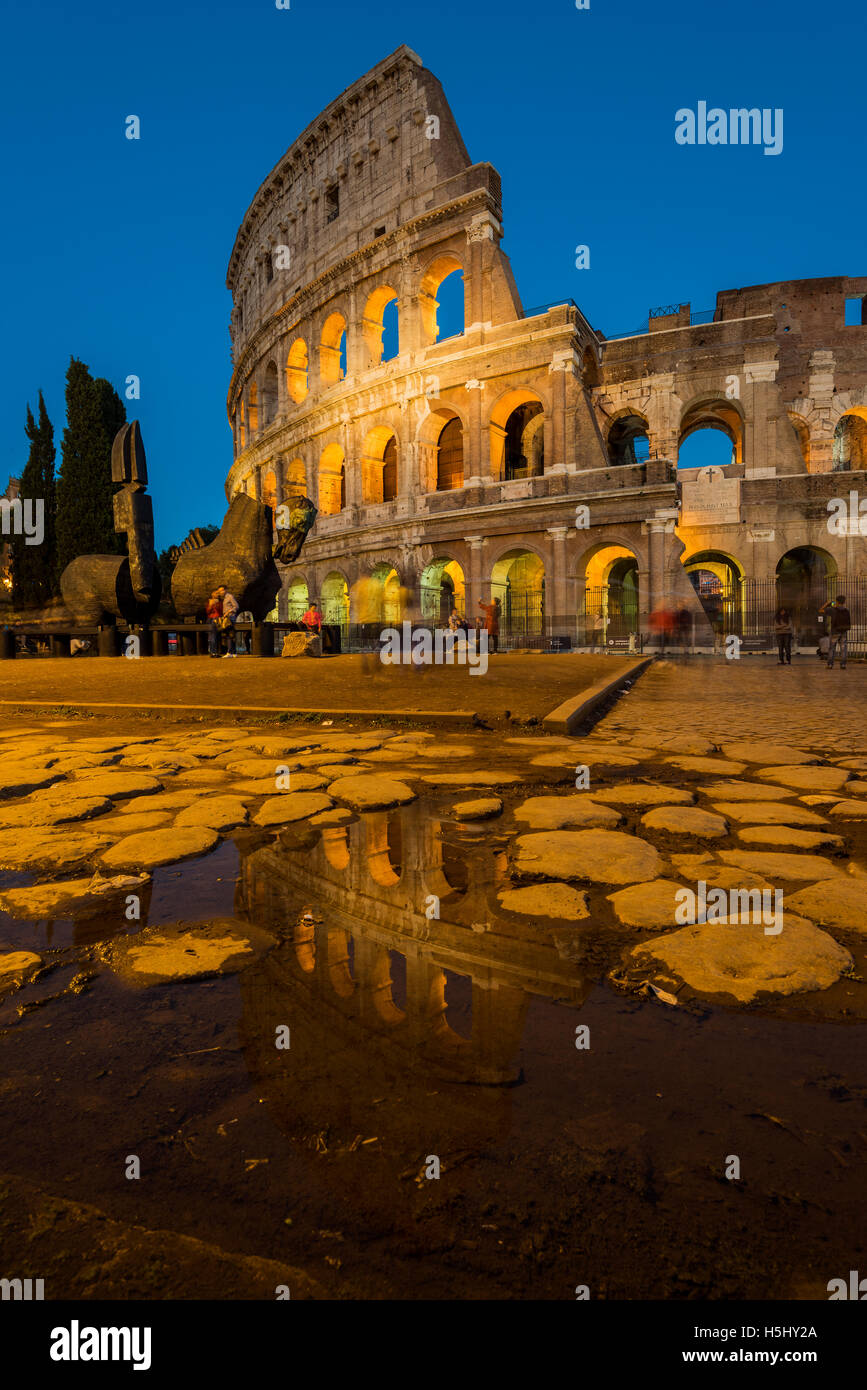 Night view of Colosseum or Coliseum reflected in a puddle, Rome, Lazio, Italy - Stock Image