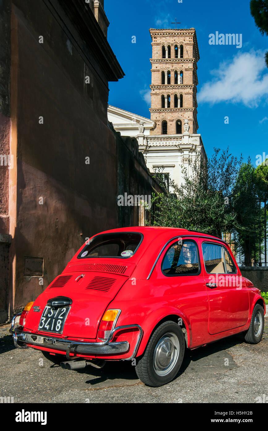 Old Fiat 500 car parked with Basilica dei Santi Bonifacio ed Alessio in the background, Rome, Lazio, Italy - Stock Image