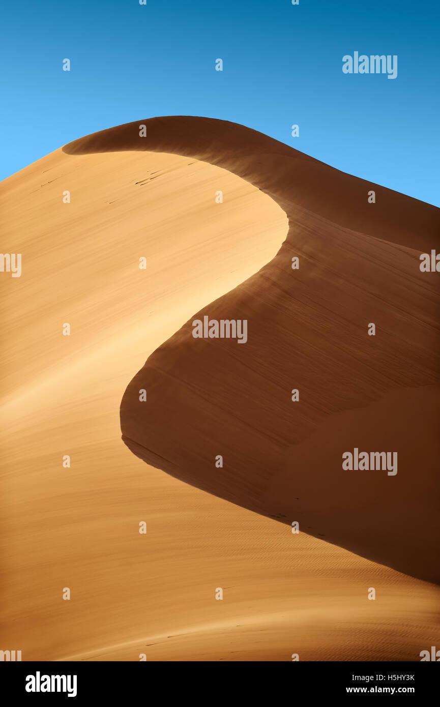sand being blown on Sahara sand dunes of erg Chebbi, Merzouga Morocco, Africa Stock Photo