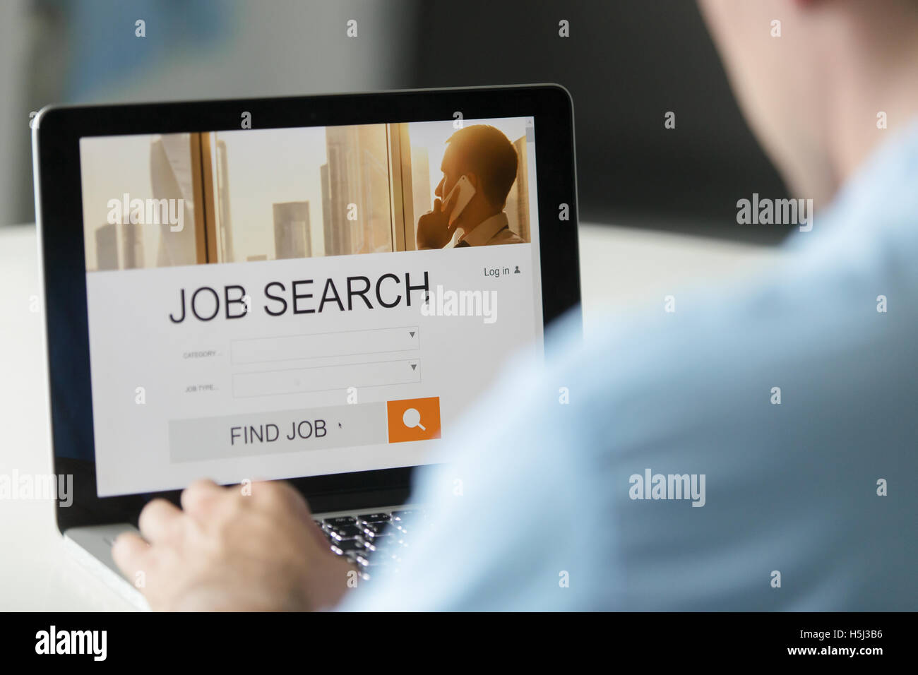 Monitor view over a male shoulder, job search title - Stock Image