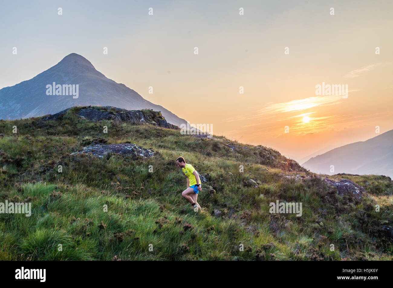 Trailrunner during sunset in the Scottish Highlands at Loch Leven, Great Brittain - Stock Image