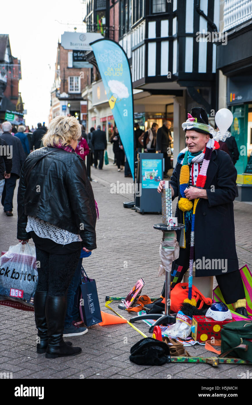 Street performer and balloon man talks to Chester shoppers - Stock Image