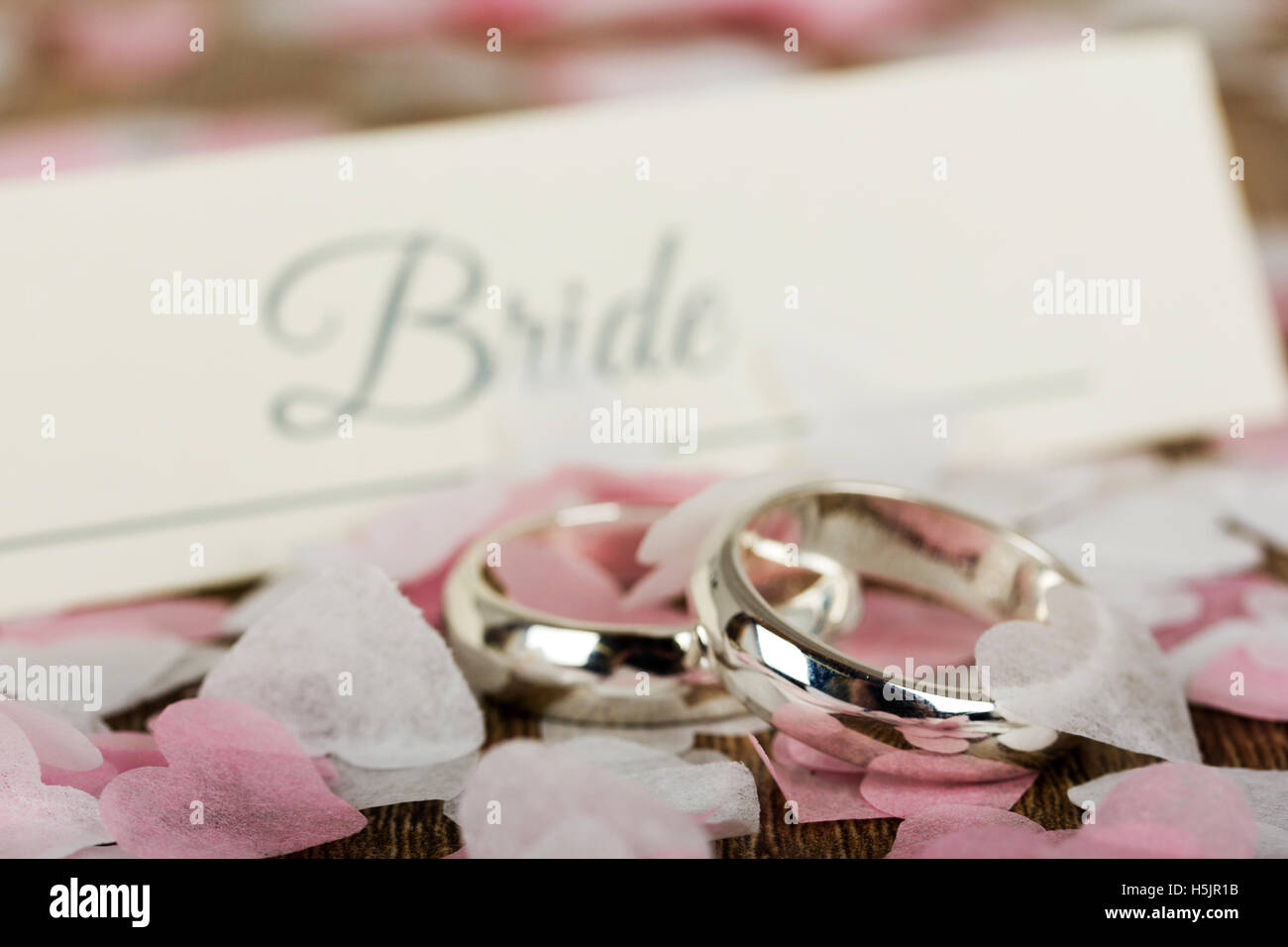 pair of white gold wedding rings on a wooden background with ...