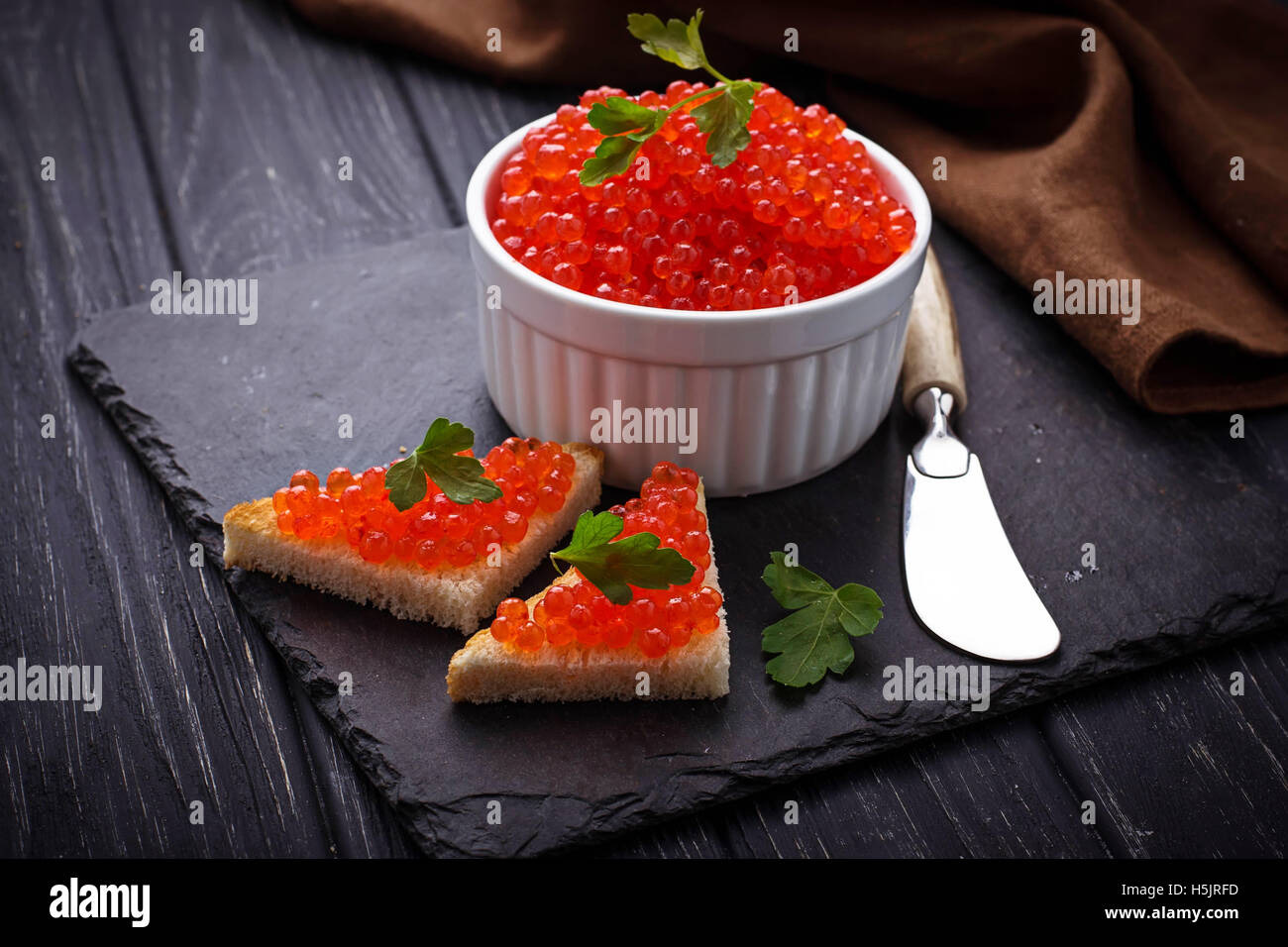 Red caviar on slate background. Selective focus - Stock Image