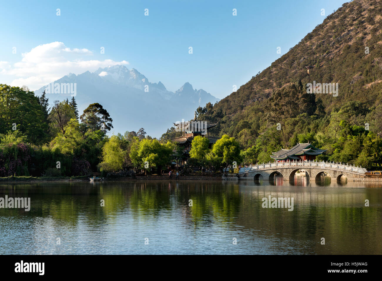 Lijiang old town scene at Black Dragon Pool Park with Jade dragon mountain in background, Lijiang, China - Stock Image