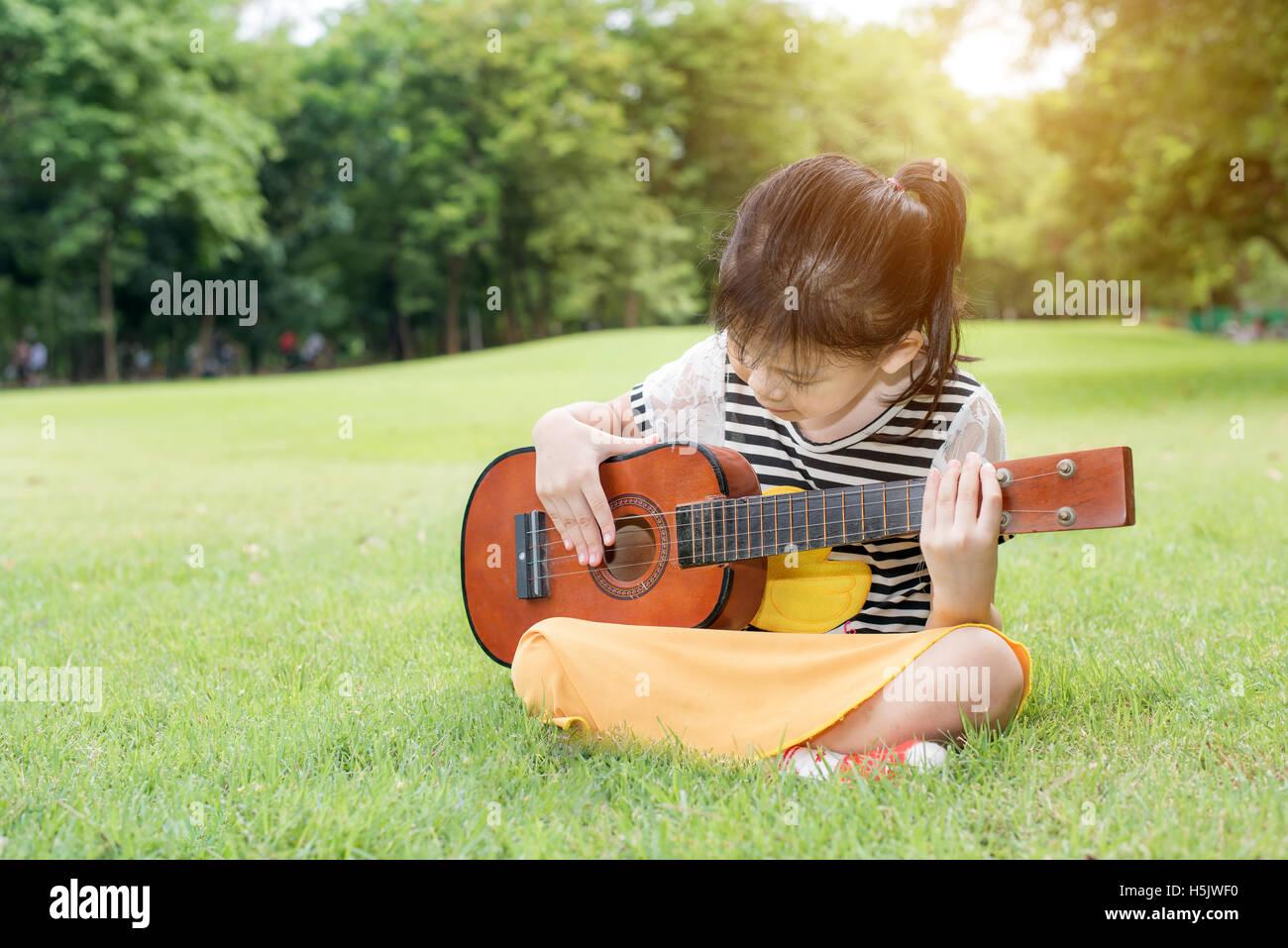 Asian little kids girl sitting on grass and play ukulele in park. Kids funny playing ukulele Stock Photo