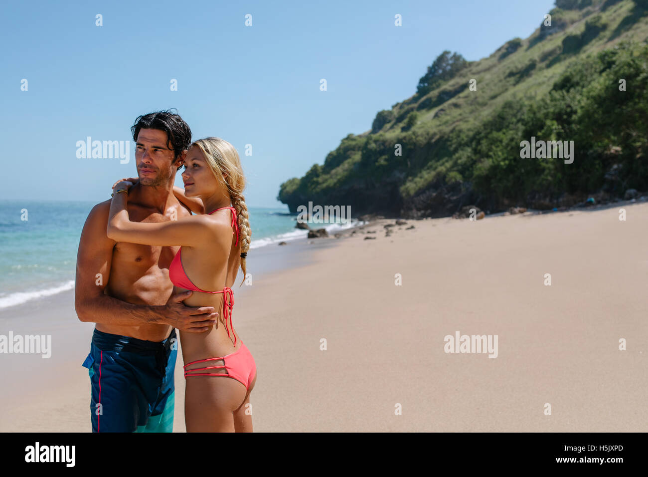 Portrait of beautiful young couple standing together on the beach and looking away. Woman in bikini and man in swim - Stock Image