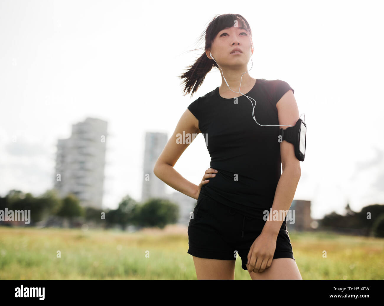 Outdoor shot of female runner standing in urban park. Chinese woman in sportswear with earphones listening to music - Stock Image