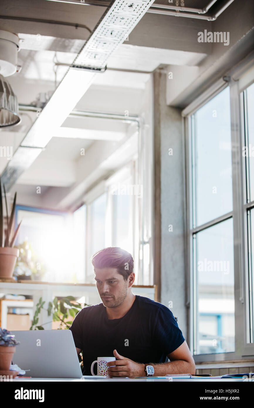 Vertical shot of young creative professional sitting at his desk with coffee and working on laptop. - Stock Image