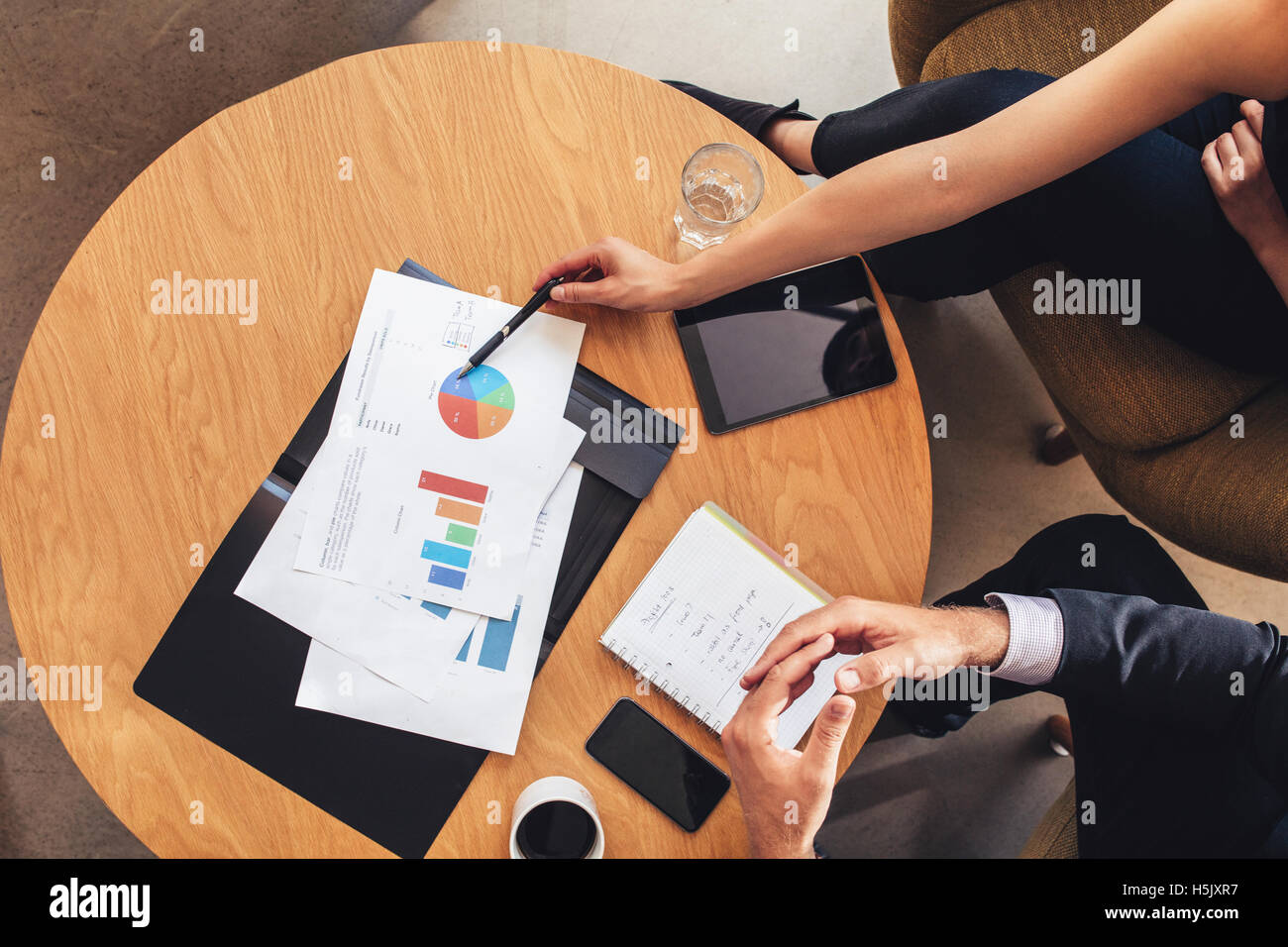 Top view of two business people working with charts around table. Businessman and woman going through business projections - Stock Image