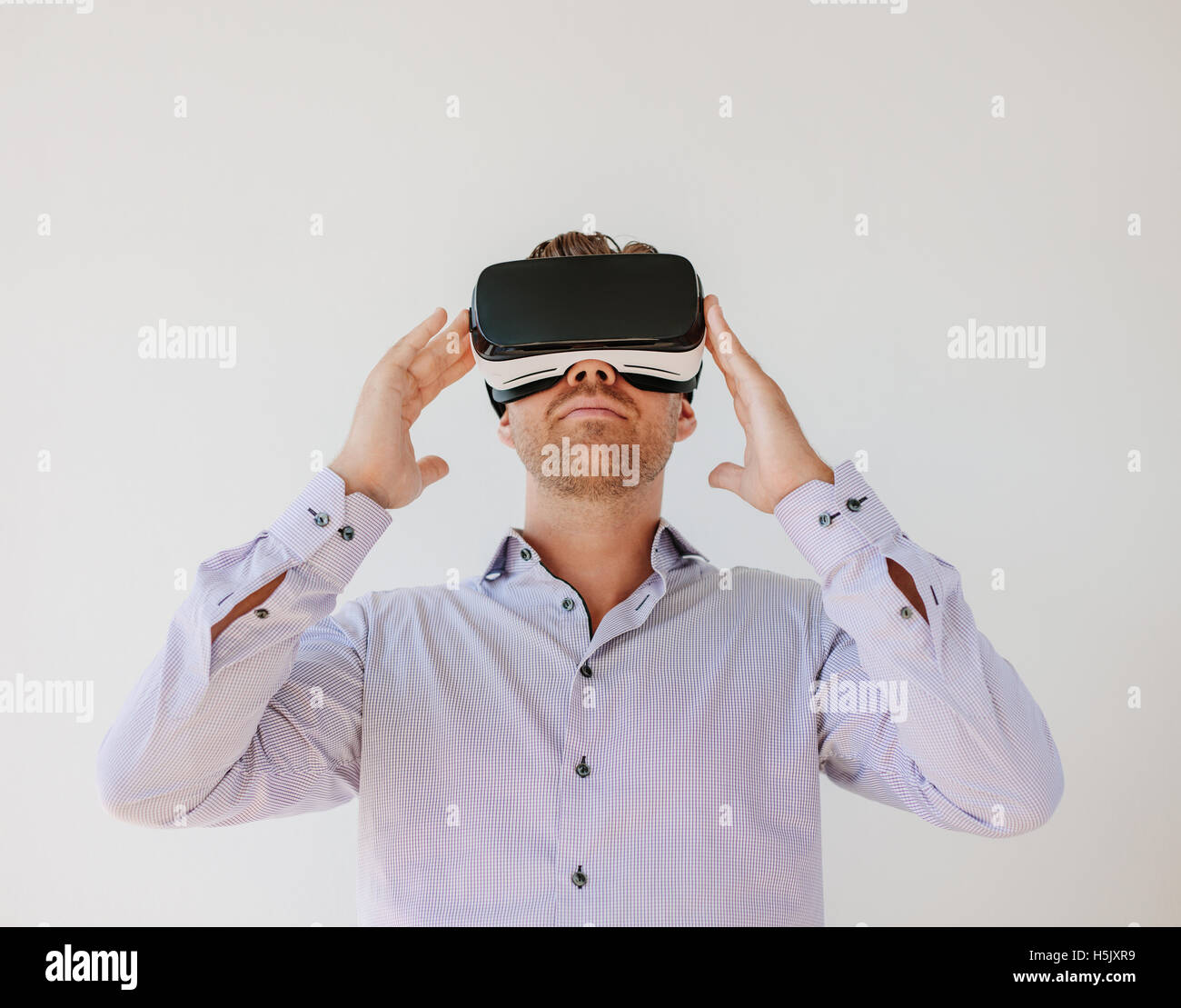 Shot of young businessman watching content on a virtual reality headset. Male model with virtual reality goggles - Stock Image